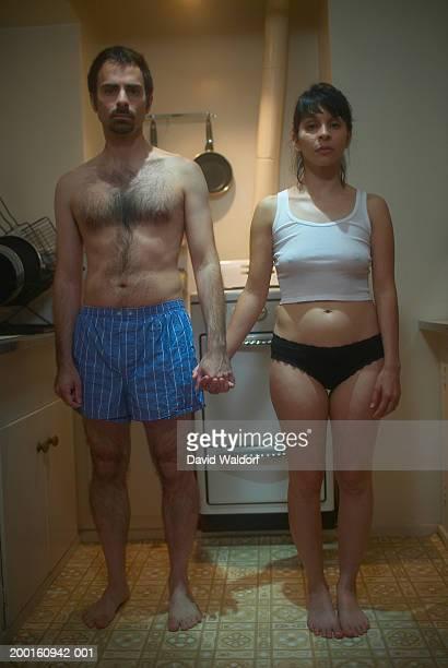 couple wearing underwear in kitchen, holding hands, portrait - homme en slip photos et images de collection