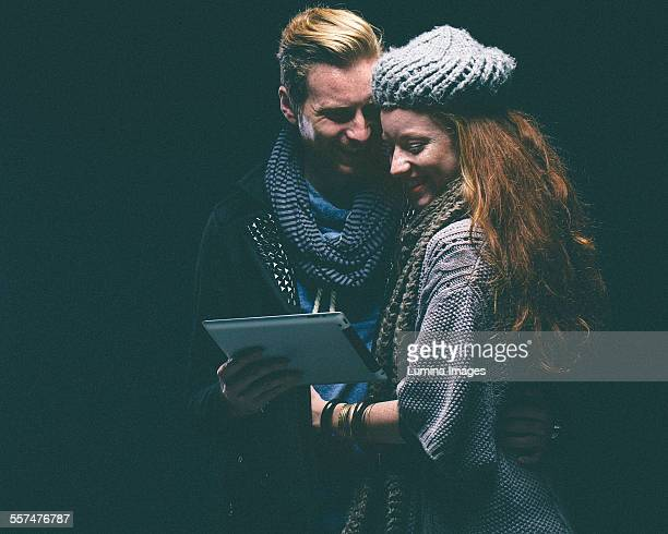 couple wearing warm clothing using digital tablet - shawl stock pictures, royalty-free photos & images