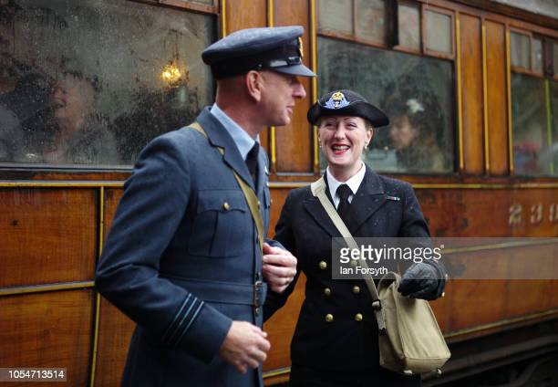 A couple wearing wartime military uniforms react as they talk at Pickering station during the North Yorkshire Moors Railway 1940's Wartime Weekend...