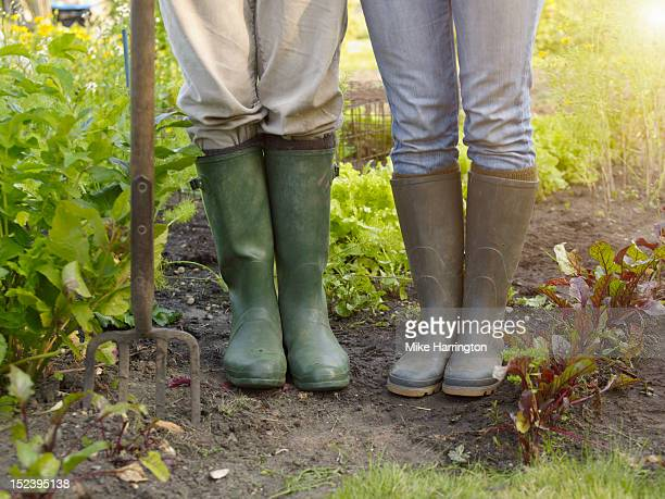 Couple wearing wellingtons in allotment