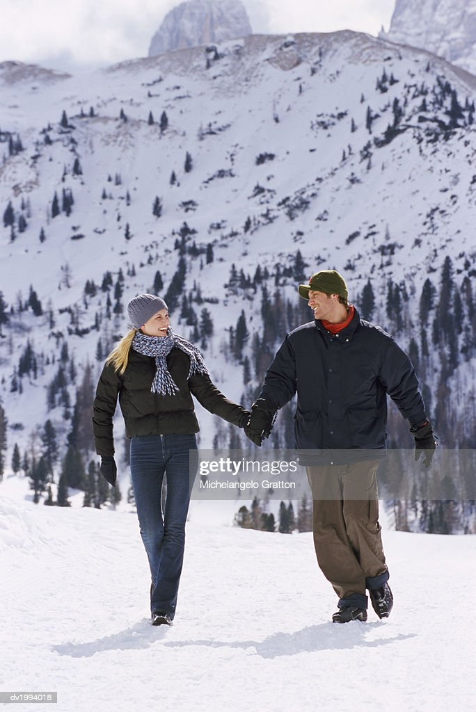 Couple Wearing Winter Clothing Walking in Snow : Stock Photo