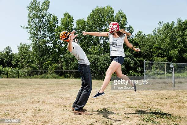 couple wearing wrestling masks play fighting - rough housing stock photos and pictures