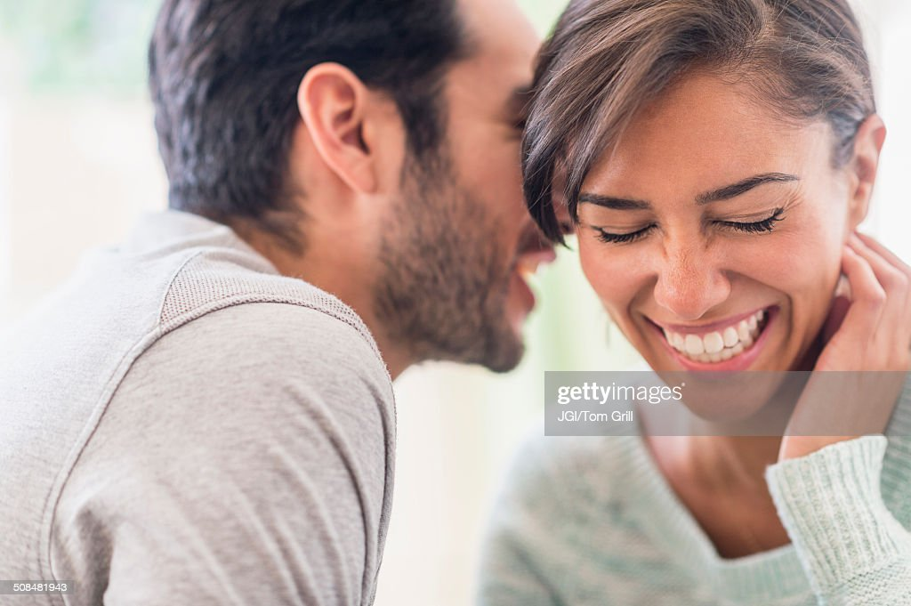Couple whispering together indoors : Stock Photo