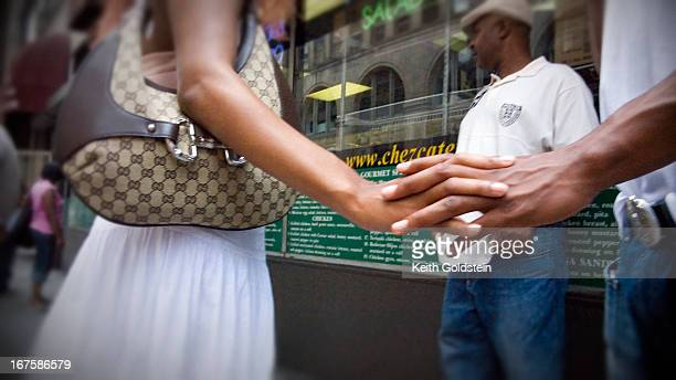 Couple, who are meeting for lunch, on street holding hands.