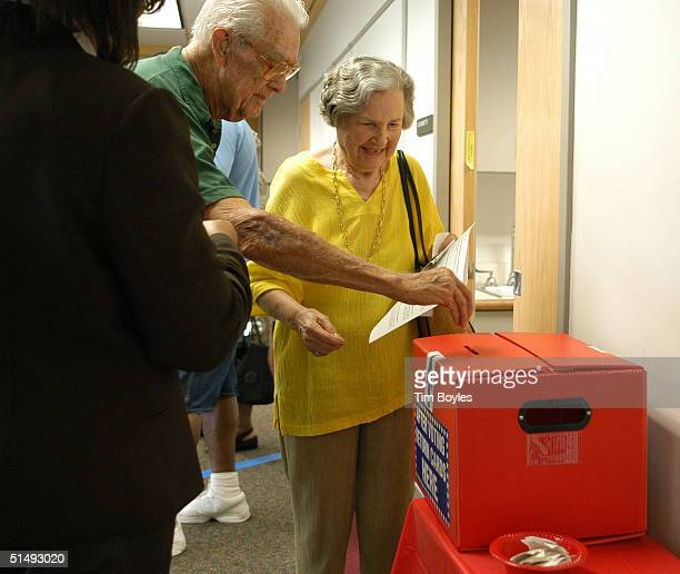 A couple who did not want to be identified by name drops their ballot receipts into a box after using an electronic machine to vote on the first day...