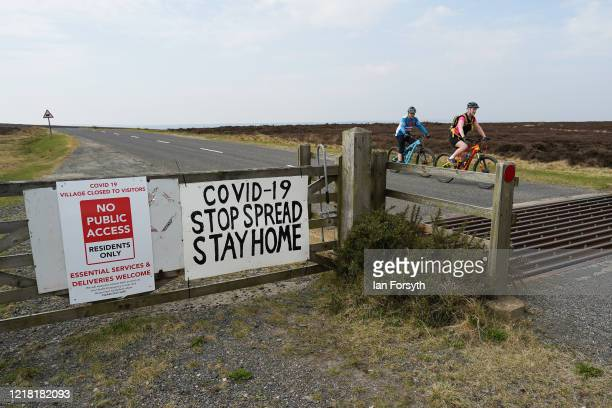 Couple who live locally take their daily exercise as signs warn visitors that a nearby village is closed as the country continues to live under...
