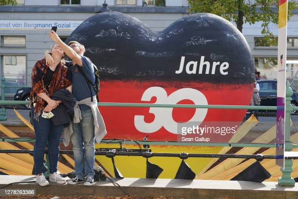 Couple, who said they did not mind being photographed, shoot a selfie in front of a giant heart painted in the colors of the German flag with the...