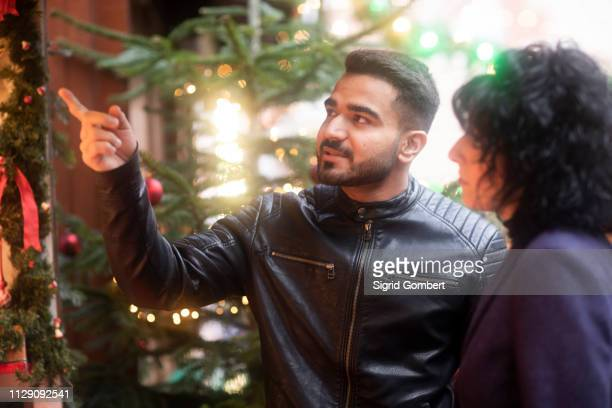 couple window shopping at christmas market, freiburg, baden-wurttemberg, germany - sigrid gombert stock pictures, royalty-free photos & images