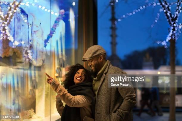 couple window shopping in city at night, new york, usa - new york weihnachten stock-fotos und bilder