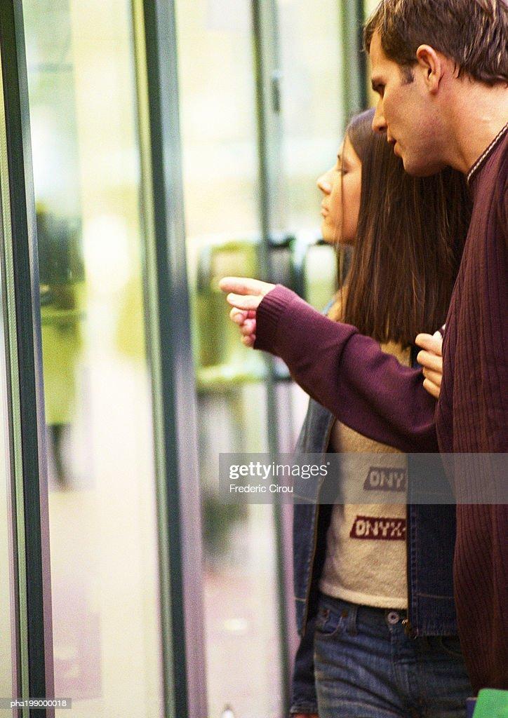 Couple window shopping, man pointing. : Stockfoto