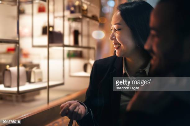 couple window shopping outdoors in winter - southern european descent stock pictures, royalty-free photos & images