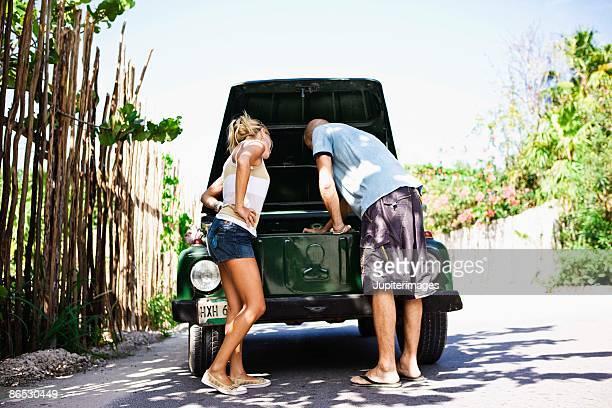 Couple with a broken down car