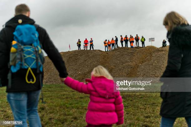 A couple with a child pass by a demonstration of Coal miners and electricity plant workers of the RWE energy company to demand a fair energy...