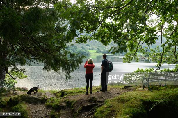 Couple with a dog admire the view over Ullswater in the Bank Holiday summer sunshine near Glenridding in the Lake District in north west England on...