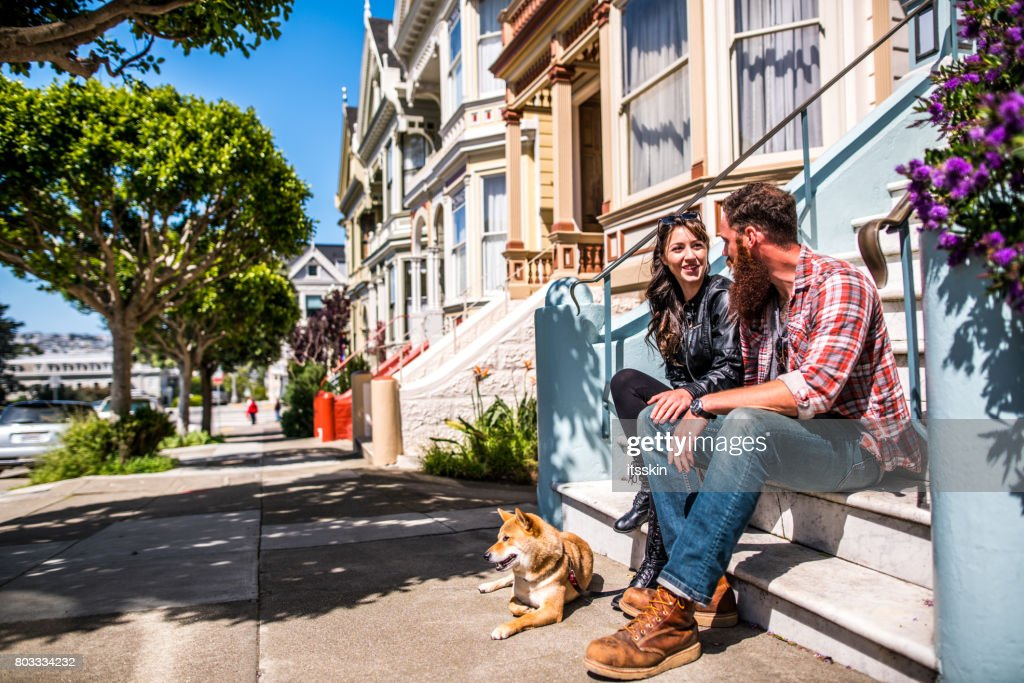 A couple with a dog on a city walk : Stock Photo