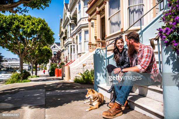 A couple with a dog on a city walk
