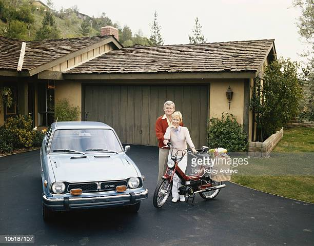 A couple with a Honda CVCC and a moped in their driveway 1980
