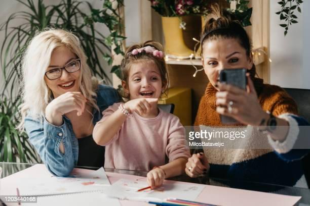 paar mit einem kind mit einem mobiltelefon - video stock-fotos und bilder