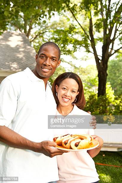 couple with a plate of hot dogs