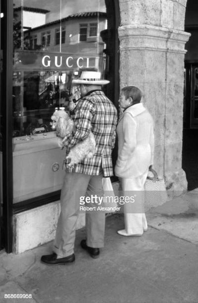 Couple with a poodle window shop in front of a Gucci store on Worth Avenue in Palm Beach, Florida, in 1982.