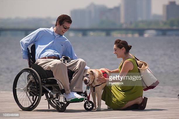 couple with a service dog on a dock - quadriplegic fotografías e imágenes de stock