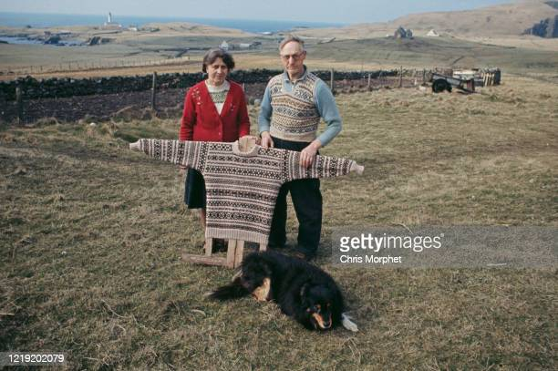 Couple with a traditional Fair Isle pattern sweater on a board, Fair Isle, Shetland Islands, Scotland, June 1970.