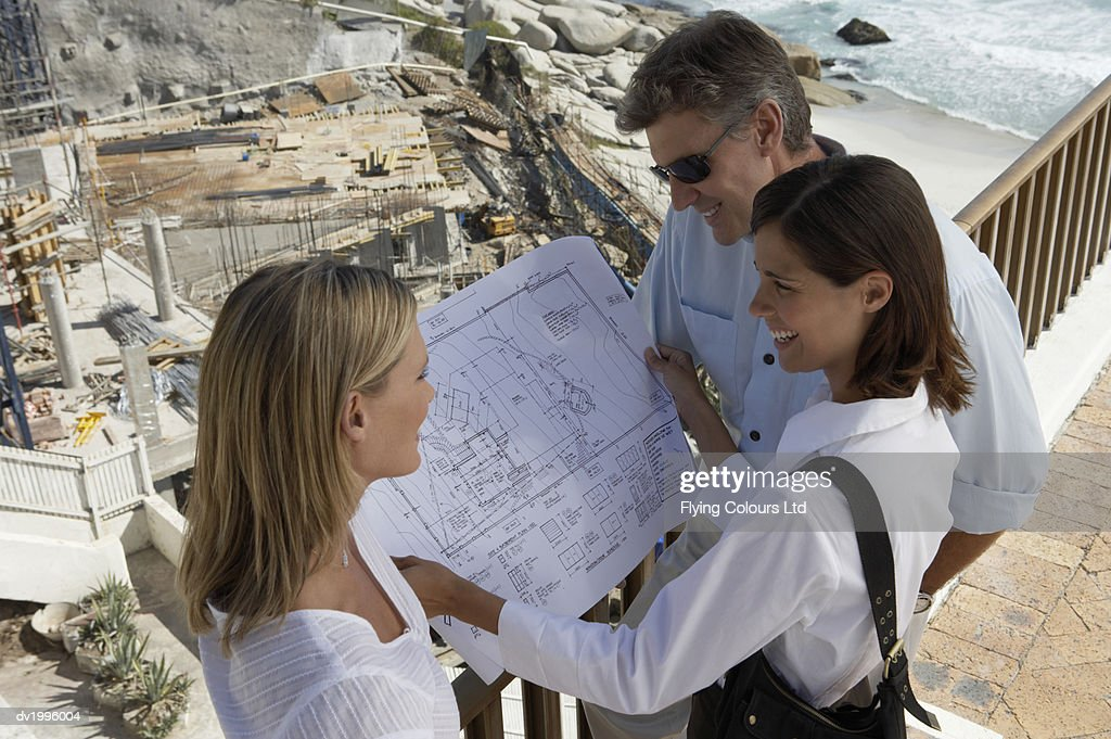 Couple With an Estate Agents on a Balcony Looking at a Blueprint : Stock Photo