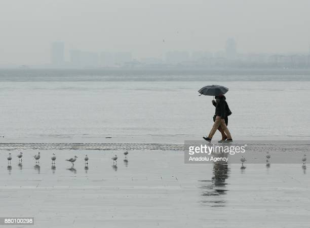 A couple with an umbrella walk on a wet floor after heavy rainfalls hit Izmir Turkey on November 27 2017 People try to prevent getting caught in...