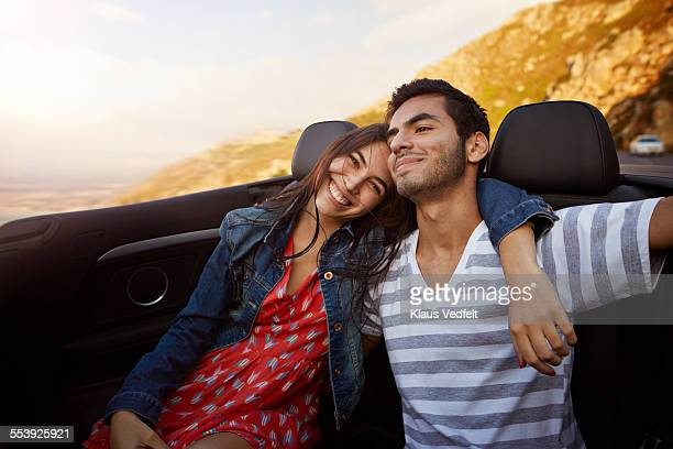 Couple with arm around each other in backseat