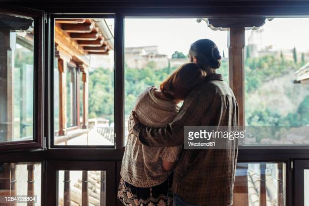 couple with arm around standing by window at home - selective focus imagens e fotografias de stock