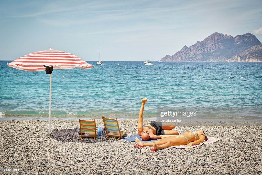 Couple with arm in the air with parasol on Porto  s beach in Corsica ... ba652f0f9cd