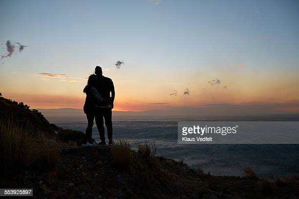 couple with arms around each other at view point - moody sky stock pictures, royalty-free photos & images