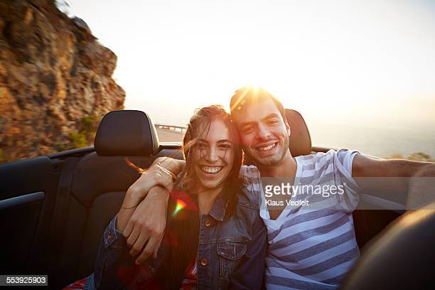 Couple with arms around each other in back of car