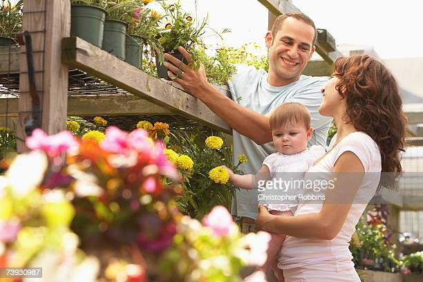 couple with baby (12-18 months) at garden centre, three quarter length - three quarter length ストックフォトと画像