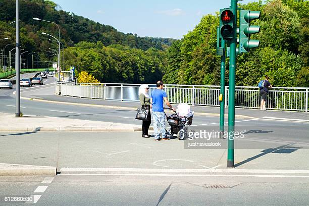 Couple with baby buggy at crosswalk