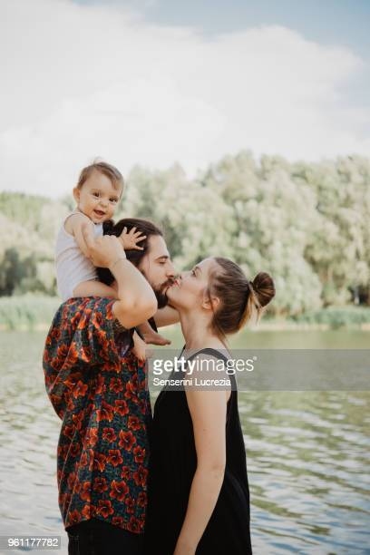 couple with baby girl by lake, arezzo, tuscany, italy - junge familie stock-fotos und bilder