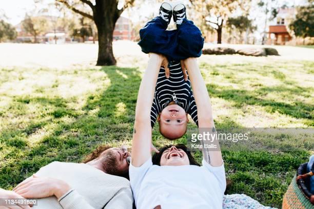 couple with baby on picnic blanket in park - nieuw leven stockfoto's en -beelden
