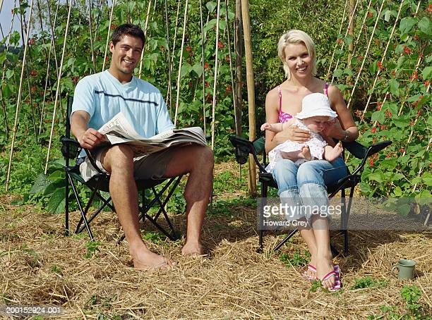 Couple with baby (3-6 months), sitting outdoors, smiling, portrait