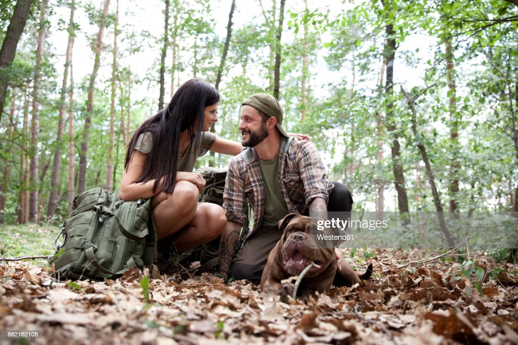 Couple with backpack and dog in forest : Stock-Foto
