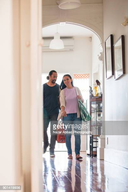 Couple with bags returning home.