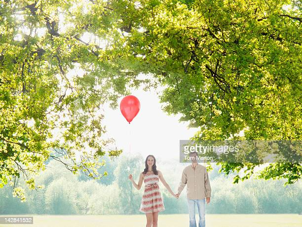 Couple with balloon holding hands under tree