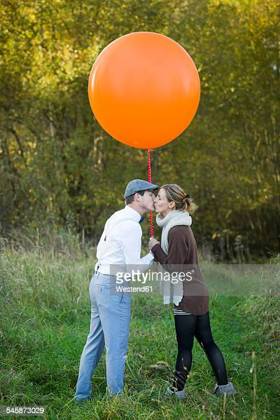 Couple with balloon on meadow kissing