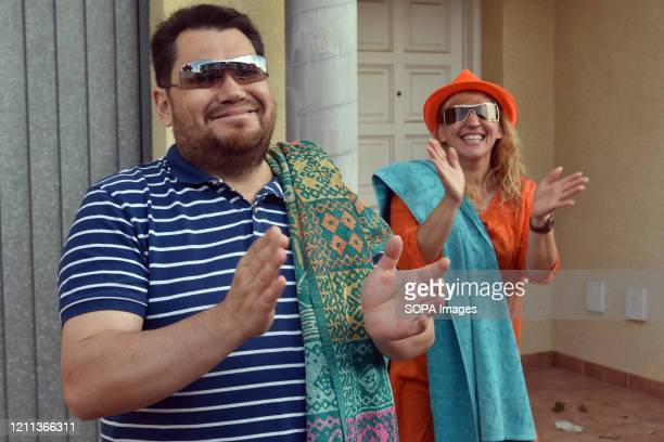 A couple with beach towels disguised as foreign tourists applaud their neighbours on the terrace of their house to encourage them during the...