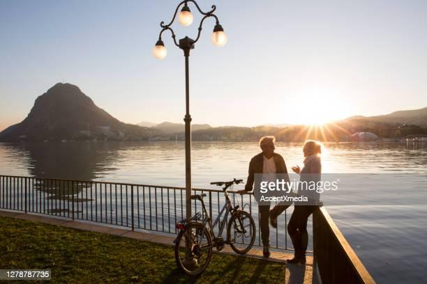 自転車を持つカップルは、日没時に湖のそばの遊歩道で会話をしています - スイス ルガーノ ストックフォトと画像