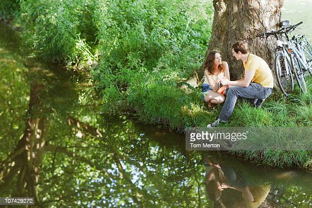 couple with bicycles sitting on riverbank together - riverbank stock pictures, royalty-free photos & images