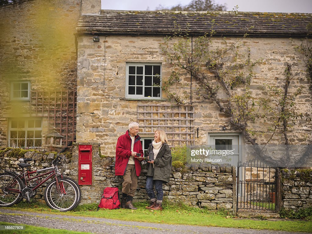 Couple with bicycles standing by dry stone wall and cottage in rural village : Stock Photo