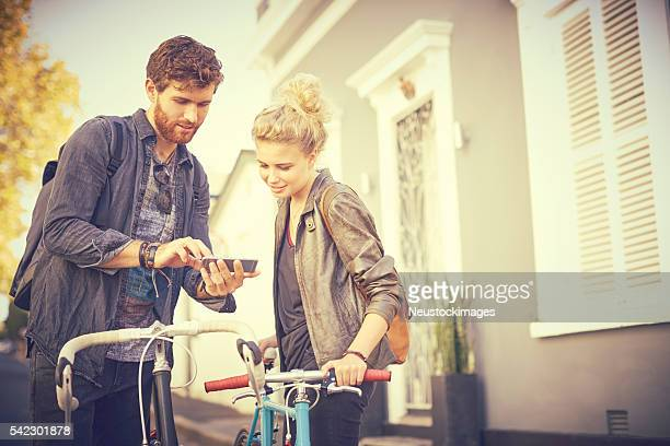 Couple with bicycles using mobile phone
