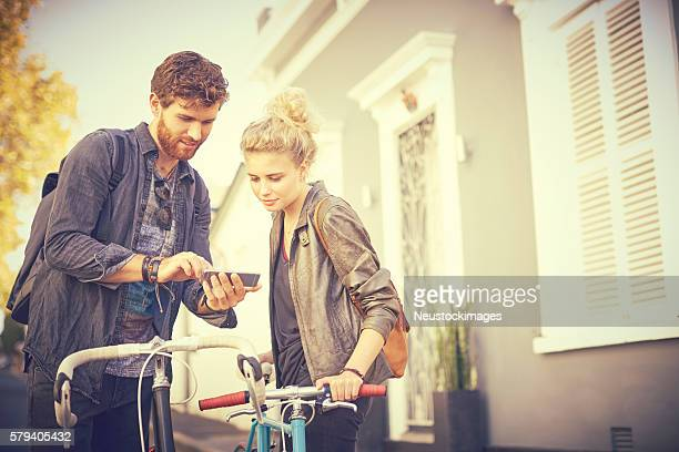 Couple with bicycles using smart phone