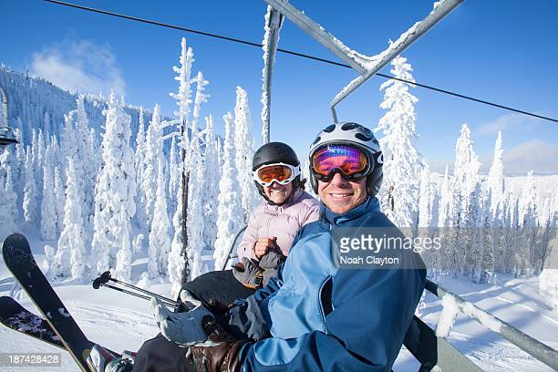 Couple with big smiles while riding chairlift