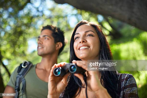 Couple with binoculars birdwatching in forest